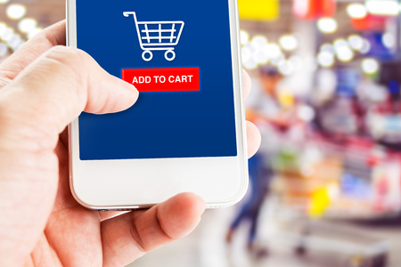 add to basket: Hand holding mobile phone with blur customer at supermarket store background,Shopping online concept,E-commerce business.