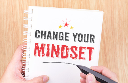 Change your mindset word on white ring binder notebook with hand holding pencil on wood table,Business concept Stock Photo
