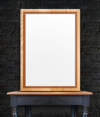 Blank wooden photo frame leaning at black brick wall on vintage wood table,Template Mock up for add design or text.