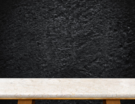 rough: Empty cream marble table top with blurred black rough stone wall,Mock up for display or montage of product.