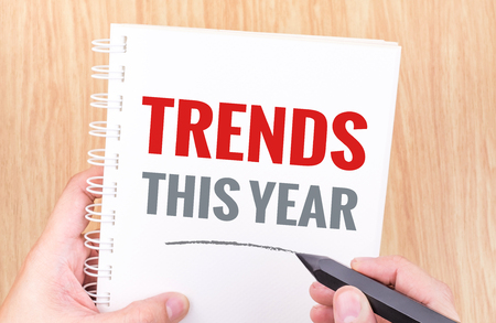 business trends: Trends this year word on white ring binder notebook with hand holding pencil on wood table,Business concept