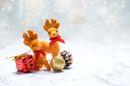 pinecones: Christmas decoration reindeer and gift,pine cone,gold ball on white marble table at blur white sparkling glitter bokeh background, Winter holiday seasonal, Leave space for adding your text.