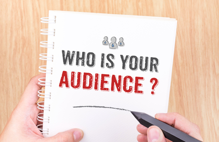 Who is your audience? word on white ring binder notebook with hand holding pencil on wood table,Business concept