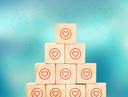 close up at heart like icon on wood cube arrange in pyramid shape on blur background ,digital marketing business concept. Stock Photo
