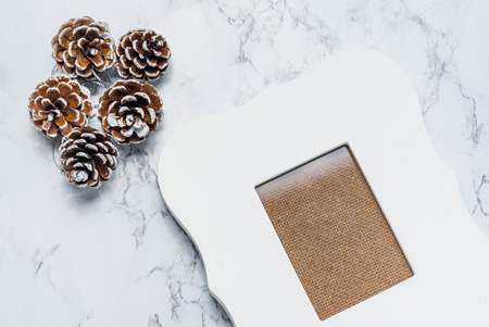 glitz: vintage white photo frame with pine cones on white marble table top,Holiday decoration card. Stock Photo