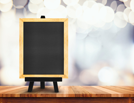 Blackboard with easel on wood table at blurred coffee shop background,Mock up for display or montage of design for online shopping promotion.
