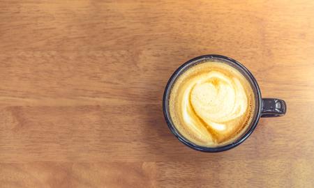 Vintage gefiltert, Top-Ansicht der weißen Kaffeetasse mit Herzform Latte Kunst auf Holz Tisch, lassen Raum für das Hinzufügen Ihres Textes.