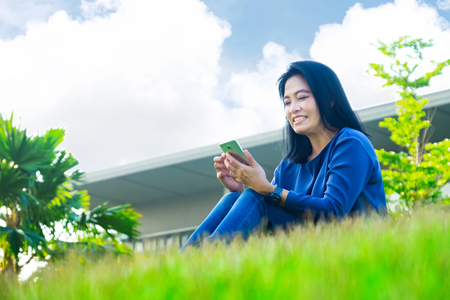view to outside: Asian woman chatting on mobile phone and smiling at screen sitting on grass outside home,Low angle view.