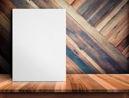 Blank White paper poster on wooden table at diagonal wood plank wall,Template mock up for adding your design and leave space beside frame for adding more text. 版權商用圖片