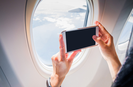 mobile phone screen: Close up woman hand holding mobile phone and take a photo outside airplane window,Blank screen for adding your design. Stock Photo