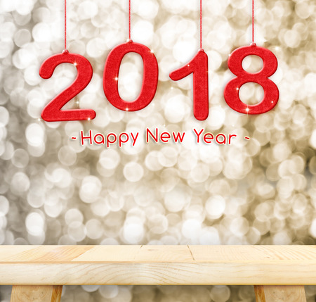 2018 Happy new year hanging over plain wood table top with blur gold sparkling bokeh light,Holiday concept,leave space for adding your design.