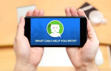 Watching two hand holding mobile phone with Chat bot and what can i help you with? with blur desk office background,Digital marketing concept. Banque d'images