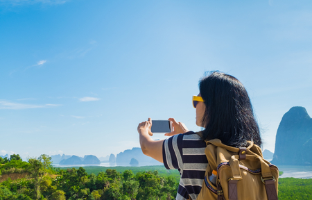 wanderlust: Young traveler woman backpacker use mobile phone take a photo of beautiful of nature at top of mountain and sea view,Freedom wanderlust concept,Khao Samed Nang Chee,Phang Nga,Thailand Stock Photo