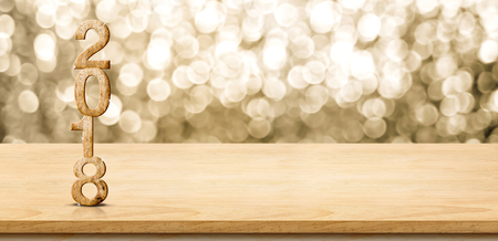 2018 new year wood number on wood table with sparkling gold bokeh wall,panoramic banner for display or montage of product. Archivio Fotografico