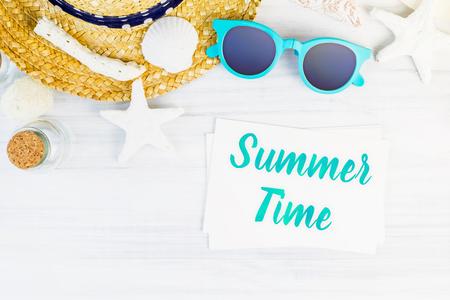 Blaues Sommerzeitwort auf weißer Karte am hölzernen Tisch mit Sonnenbrille, Strohhut, Starfish, Draufsicht der Glasflasche, Ferienkonzept Standard-Bild - 80571286