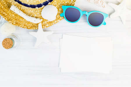 adding: Summer Beach accessories (White sunglasses,starfish,straw hat,shell) and photo frame on white plaster wood table top view,Summer vacation concept,Leave space for adding your photo.