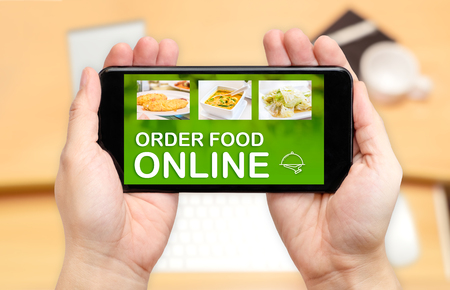 Watching two hand holding mobile phone with order food online word on screen and blur desk office background,Digital restaurant concept. Stock Photo