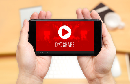 Watching two hand holding mobile phone with play and share icon on screen and blur desk office background,Digital content concept.