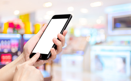 store shelf: Hand click mobile phone with blur department store background bokeh light,White screen mock up template for adding your design or your text.