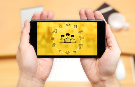 Watching two hand holding mobile phone with digital advertise marketing features on screen and blur desk office background,Digital content concept.