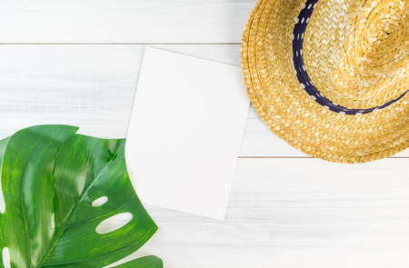 Blank white paper card on wood table top view with straw hat and blur foreground tropical palm leaf ,Summer vacation concept,Mock up template for adding your design or text.