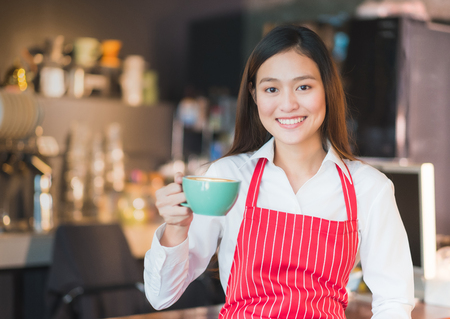 Asian female barista wear red apron holding hot cappuccino coffee cup menu at counter bar with smile face,cafe service concept.