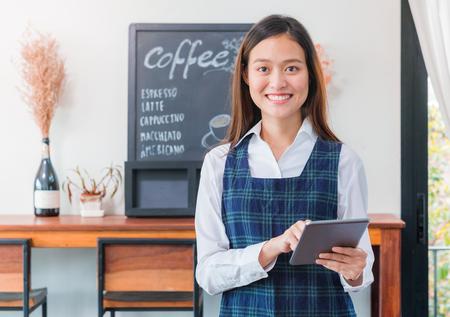 El barista femenino asiático lleva el menú azul del café de la tableta del control del delantal con la cara sonriente en orden que espera del café del cliente, concepto del dueño de negocio del café.
