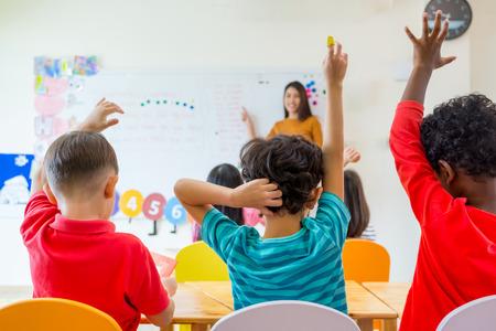 Enfant d'âge préscolaire lever le bras pour répondre à la question de l'enseignant sur le tableau blanc dans la salle de classe, le concept de l'éducation de la maternelle. Banque d'images - 84418282