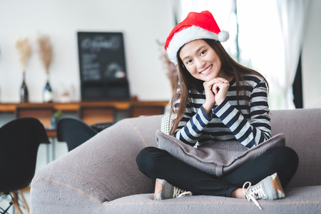 Asian teenage girl sitting cross-legged on sofa with Christmas hat and smile face and  resting her chin on her hands at home ,Celebrate New year and Christmas holiday concept.