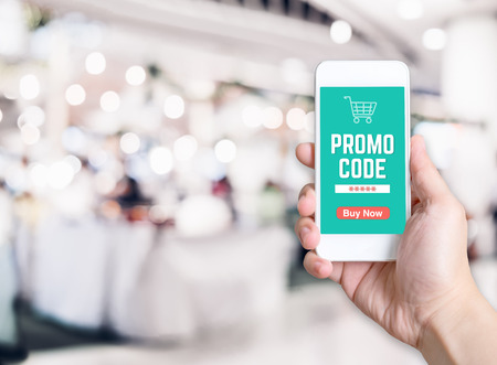 Hand holding mobile phone with promo code word with blurred store background with bokeh light ,internet marketing concept,E-commerce. 免版税图像