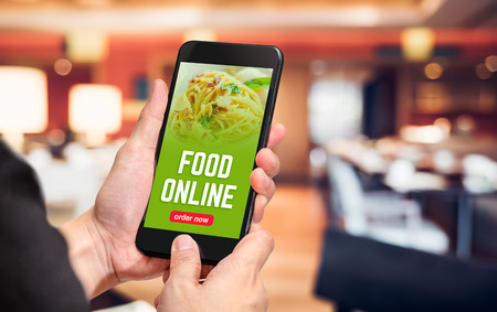Close up hand holding mobile phone with order food online word on screen with blur restaurant bokeh light background,online food marketing concept Archivio Fotografico
