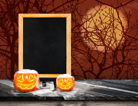 easel: Blackboard with easel on grunge plank wooden and pumpkin with smoke on table top at spooky dead tree and full moon,Halloween invitation card,Template mock up for display or montage of product. Stock Photo