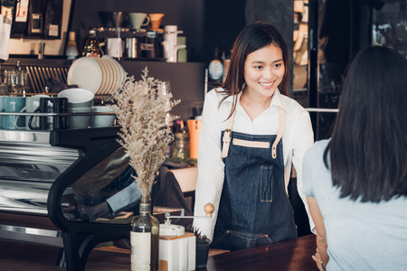 Asian woman barista wear jean apron holding coffee cup served to customer at bar counter with smile emotion,Cafe restaurant service concept,Owner small business concept. Archivio Fotografico