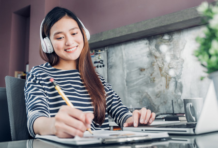 Young asian casual businesswoman listening music and writing report on office desk,work at home with online e-commerce job concept.
