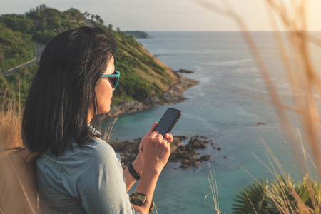 Young traveler woman use mobile phone taking of photo at beautiful of nature at top of mountain and sea view,travel wanderlust backpacker concept. Stock Photo