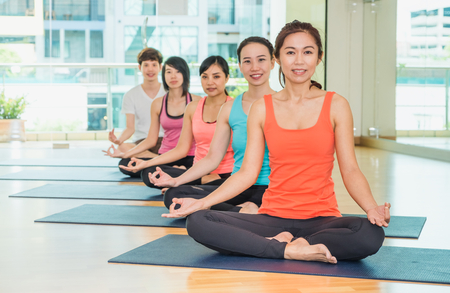 woman mirror: Yoga class in studio room,Group of people doing lotus pose with clam relax emotion,Meditation pose,Wellness and Healthy Lifestyle Stock Photo