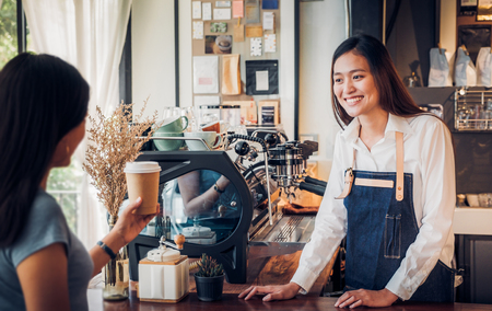 Asian woman barista wear jean apron served to go coffee cup  to customer at bar counter with smile emotion,Cafe restaurant service concept,Owner small business concept.