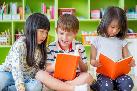 Niños sentados en el piso y leyendo el libro de cuentos en la biblioteca preescolar, concepto de educación escolar de jardín de infantes Foto de archivo