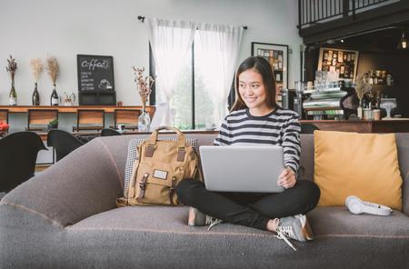 Aziatisch tienermeisje die laptop computer en het luisteren muziek op bank met gelukkig het glimlachen gezicht met behulp van bij koffiewinkel, Digitale leeftijdslevensstijl.