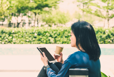 connection connections: Woman in causal cloth holding to go coffee cup and use tablet computer outside house at garden,digital lifestyle.