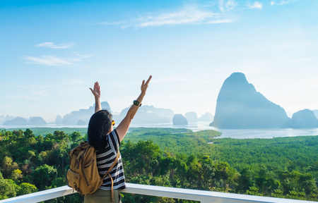 Happy young traveler woman backpacker raised arm up to sky enjoying a beautiful of nature at mountain panorama view point and sea,Freedom wanderlust,Khao Samed Nang Chee Viewpoint,Phang Nga,Thailand