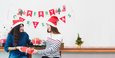 Asia girl friends wear santa hat in merry christmas party and exchange red gift box each other with smiling face,Xmas gift giving,Lovely lesbian couple,Leave space for adding text Foto de archivo