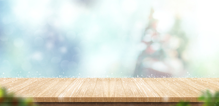 Empty wooden table with abstract blur christmas tree and snow falling background with bokeh,Holiday backdrop,Mock up banner for display of product for promotion online. Archivio Fotografico