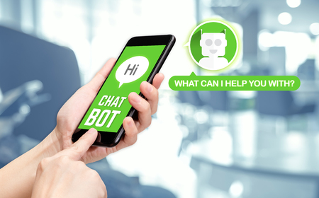 Hand holding mobile chat with bot on mobile message app with blur office background,artificial intelligence(ai) bot.