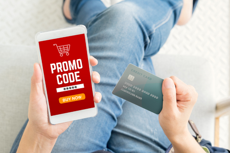 Close up woman hand holding credit card and mobile phone with promo code on online shopping app,Digital marketing concept.