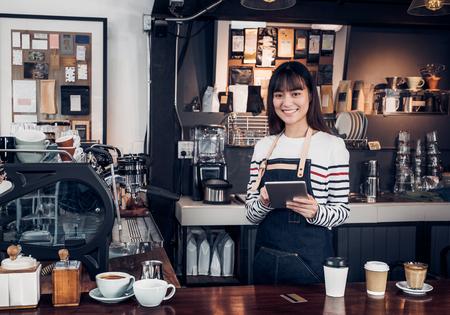 kobieta barista przyjmuje zamówienie z tabletem, azja kelnerka za pomocą urządzenia cyfrowego w kawiarni biznes w barze przy barze w kawiarni, moder właściciel żywności założenie firmy