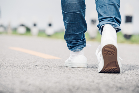 finding your way: Close up woman wear jean and white sneaker walking forward on highway road in sunny day,Alone travel or solo traveler concept.