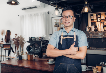Male Barista thumbs up in front on cafe counter bar with customer sitting inside coffee shop,Good owner food and drink business,success shop.