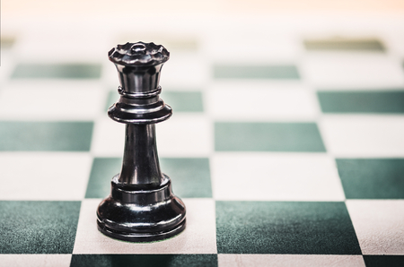 Close up black queen chess on green checkerboard,Female leader. Stock Photo