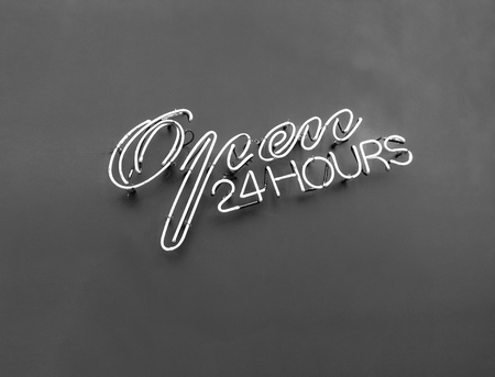 open 24 hours neon sign on wall ,Black and white color tone. Stock Photo
